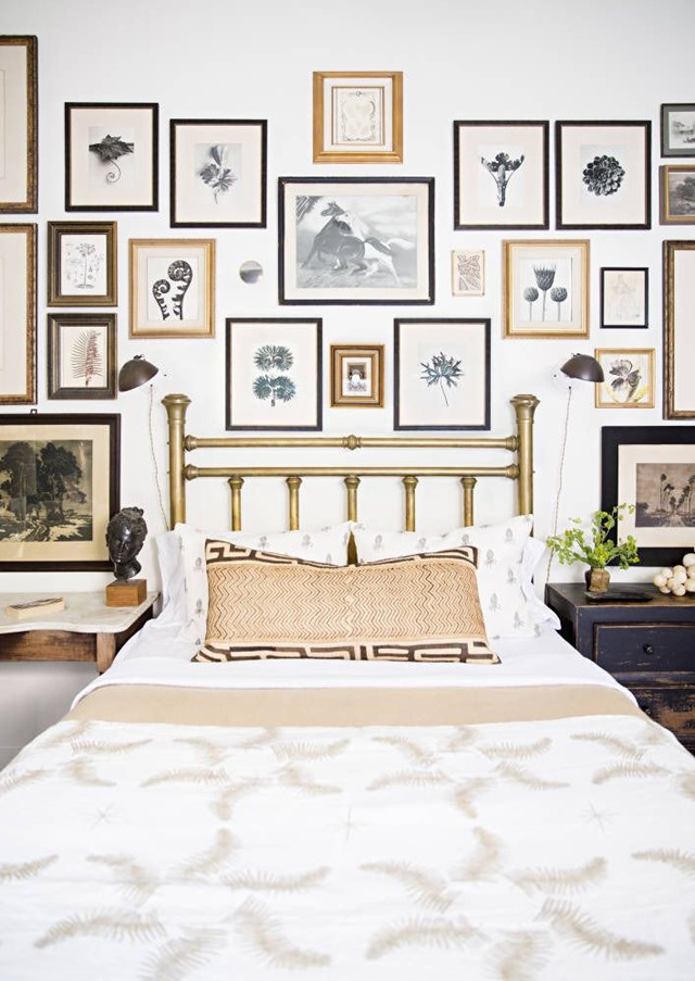 Neutral botanicals on gallery wall above bed